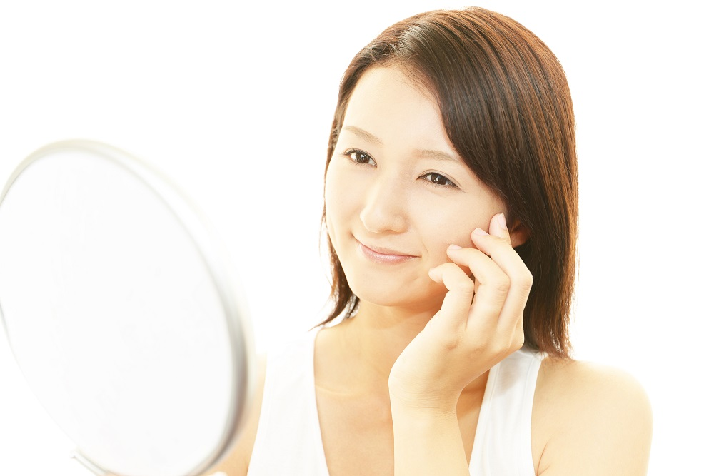 woman looking in mirror with waxed face